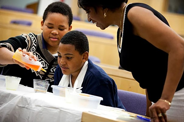 Students Hughlando Simonds and Marquise Lamb enjoy a science experiment with teacher Ada Garner.