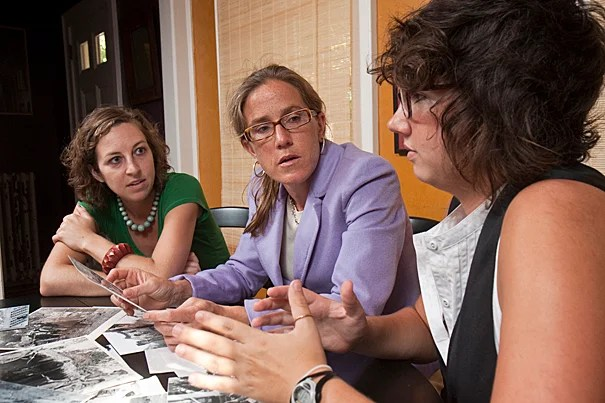 """Professor of history Caroline Elkins (center), doctoral student Erin Mosely (left), and recent graduate Megan Shutzer examine photos collected for an upcoming exhibit that will tell the story of Kenya's break from colonial Britain. """"It's not a '1960s, we all fight for freedom' [story]. It has complexity,"""" Elkins said."""