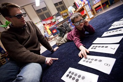 """Sean Andersson (left) works on a math problem called """"X-ray vision"""" with his son Ethan, 5, at the Gardner Pilot Academy. Math Night was the latest of Harvard's many collaborative efforts with the school."""