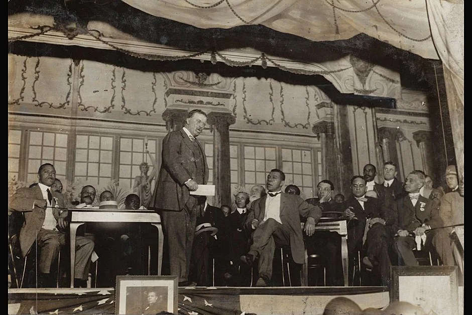 Booker T. Washington (center, right) listens to Theodore Roosevelt (center, left) deliver a speech on stage in Tuskegee, Alabama. On June 24, 1896, Washington became the first African American to receive an honorary degree from Harvard University. Photo by American Press Association. Photo credit: Theodore Roosevelt Collection (560.52 1905-168)