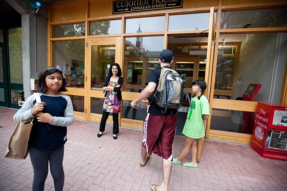 Autumn Galindo (left) waits for her ride after visiting her friend, Currier resident Mara Cavallaro, who is holding the door for a student. Mara's mother, House Master Nadejda Marques (center), looks on. Rose Lincoln/Harvard Staff Photographer