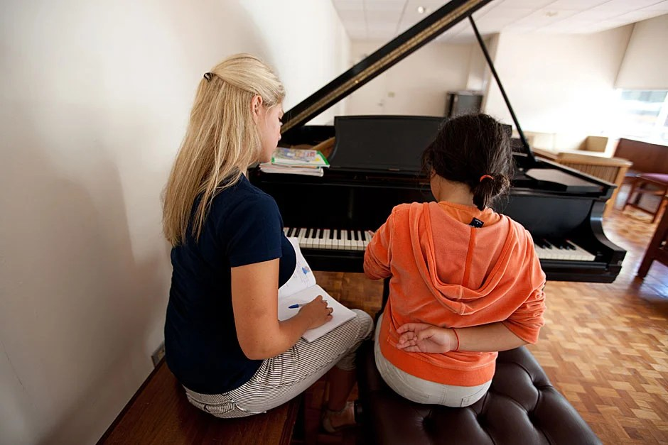 Lindsey Brinton '12 teaches Mara to play the piano during their babysitting sessions at Currier House, where both reside. Rose Lincoln/Harvard Staff Photographer