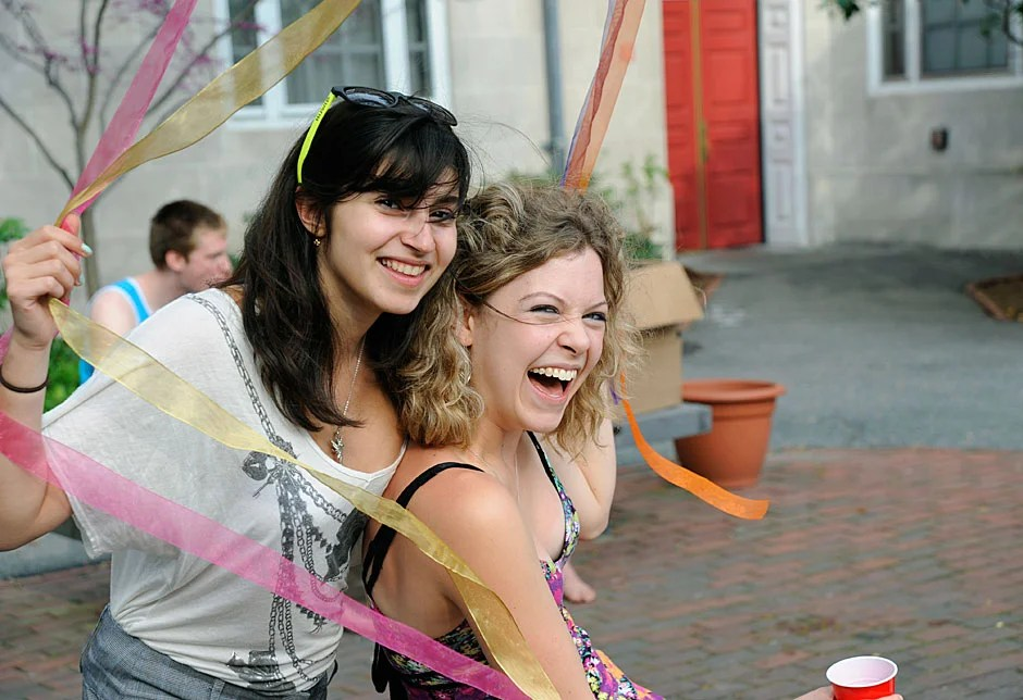 Liora Simozar '13 (left) and Tess Hellgren '11 share a laugh while getting tangled up in wind-blown ribbons in the courtyard during festivities at the annual Dunster House goat roast. Jon Chase/Harvard Staff Photographer
