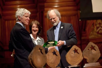 "Harvard Kennedy School alumnus Lester Brown, M.P.A. '62 (left), received the first-ever Distinguished Service Award. Brown, who was introduced by Professor Jim McCarthy (right) as an ""environmental Paul Revere,"" spoke for several minutes about trends that have contributed to a reduction in carbon dioxide emissions in the United States after a peak in 2007. Angela Crispi, associate dean for administration at Harvard Business School, looks on."