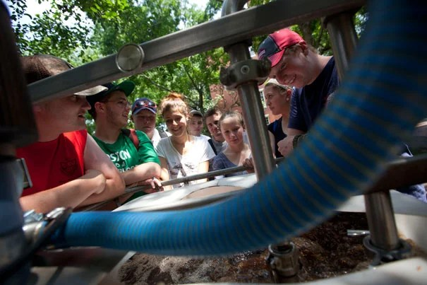"""Norfolk County Agricultural High School students watch the brewing of organic fertilizer """"tea"""" by Harvard Landscape Services during a visit to Harvard Yard. The field trip was part of a four-week program in partnership with the Arnold Arboretum."""