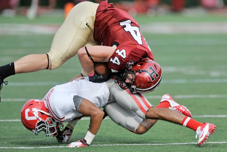 After catching a pass, Crimson tight end Kyle Juszczyk `13 ends up on top after a low tackle by a Cornell defender.
