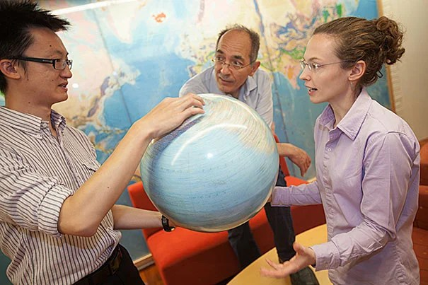 Jerry X. Mitrovica (center), professor of geophysics, and Jessica Creveling illustrate their research using a model of the Earth inside the Geological Museum at Harvard. Ngai Ham Chan, a research assistant in the Department of Earth and Planetary Sciences, joined them in the project.