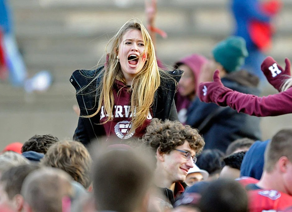 A Crimson fan riding a wave of ecstatic students on the field shrieks out in jubilation as Harvard defeats Yale, 28-21, in 2010.