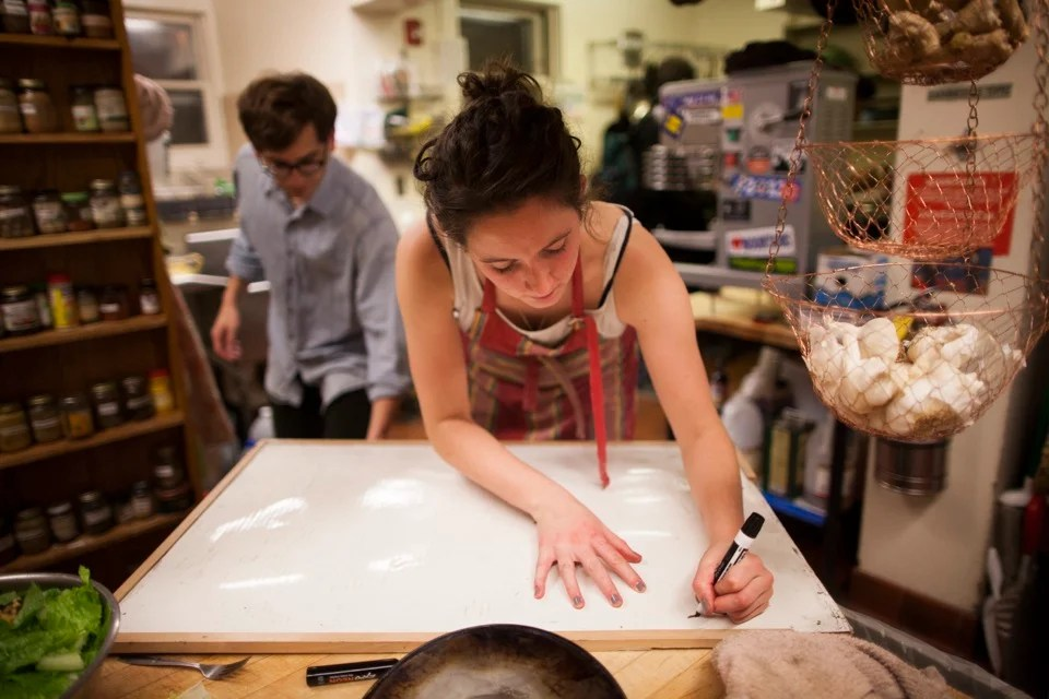 Alex Traub '13 (left) looks on as Zoe Tucker '13 writes the dinner menu on the whiteboard. The menu includes honey-lemon-cayenne-roasted broccoli, grilled tempeh marinated in soy sauce and maple syrup, eggplant coconut curry, farro with roasted beets and apples, green salad, and chocolate cupcakes.