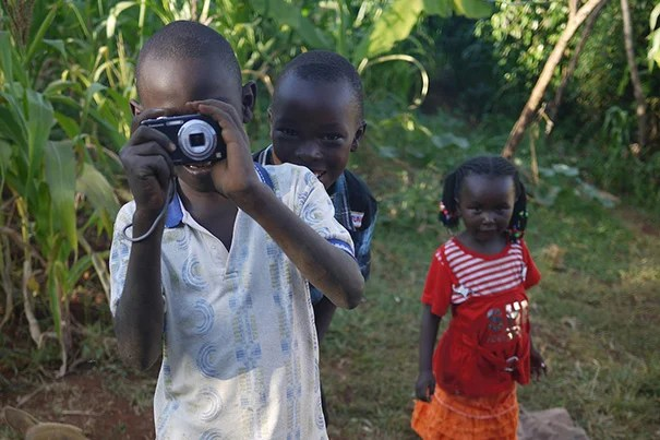 """Children at play in Meru, Kenya. The hope and riches of Africa, the """"continent of the future,"""" are expressed here: youth, education, and the embrace of technology."""