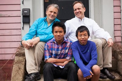 """This year, thanks to a change in Harvard policy, same-sex married couples won't have to pay additional federal taxes on their health coverage. """"I was touched,"""" said Kevin Patton-Hock (clockwise from left), a full-time parent to his and husband Arthur Patton-Hock's two sons, Chet and Mao. """"I thought it was really nice, and just a beautiful thing to see everyone treated the same."""" Arthur has worked for Harvard for more than 27 years."""