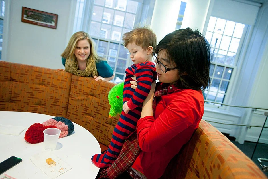 """Resident Tutor Marie Dach (from left) watches her 1-year-old, Owen, being entertained by Yi-Jou Chiang during """"PfoHo Fridays,"""" a weekly tradition in the Junior Common Room at Pforzheimer House on Radcliffe Quad. Rose Lincoln/Harvard Staff Photographer"""