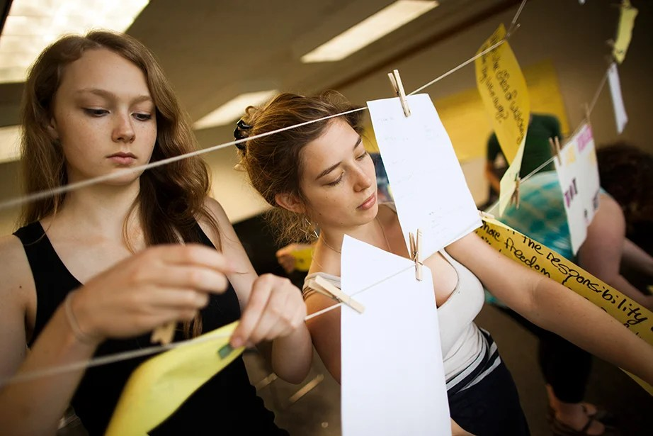 Grace VanBuskirk (left) and Leah Cohen hang their writing exercises.