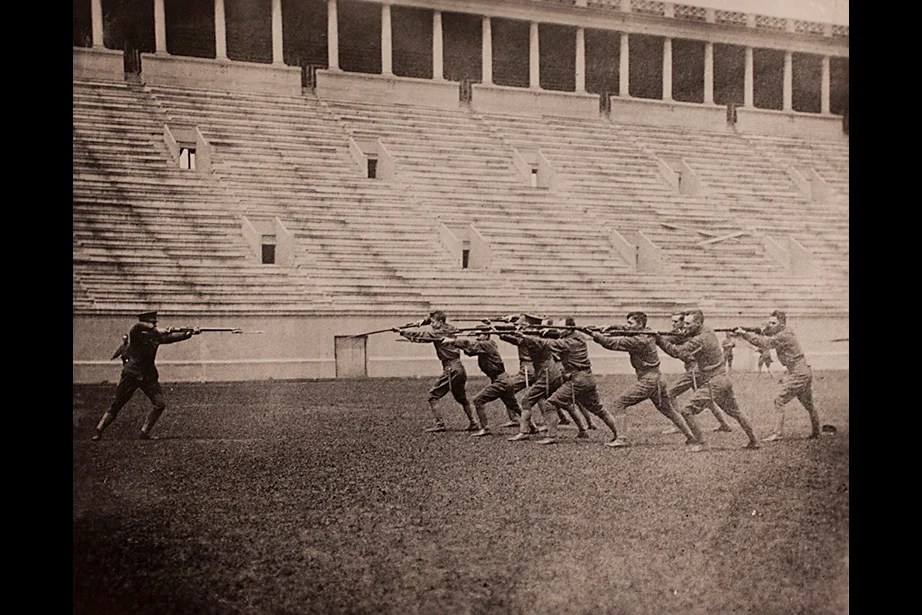 Copy image of historical material gathered from Harvard University Archives regarding the university's history with ROTC. The image inscription reads, Bayonet Drill, Harvard ROTC at Stadium, 1917-1918. Stephanie Mitchell/Harvard Staff Photographer