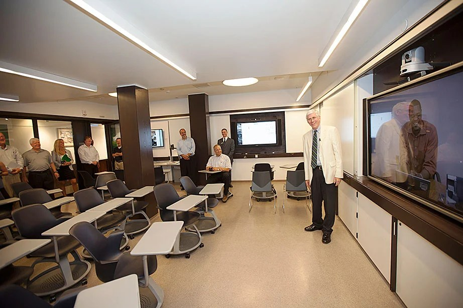 Robert Doyle, associate dean of the Faculty of Arts and Sciences, demonstrates the features of a smart classroom as FAS Dean Michael D. Smith looks on.
