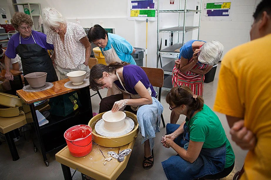 Ceramics instructor Monica Ripley (center) demonstrates throwing techniques with porcelain clay.