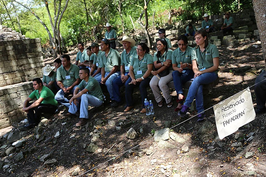 Members of the field team Proyecto Arqueológico Rastrojón Copán (PARACOPAN), composed of local Copán residents and Harvard students, listen to opening remarks during the site's official unveiling in August.