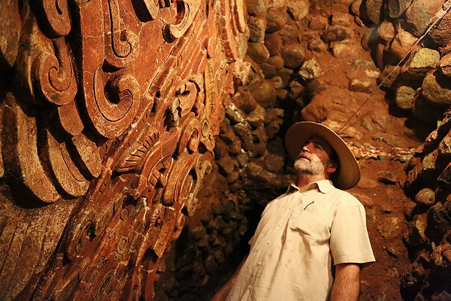 """William Fash, Harvard's Bowditch Professor of Central American and Mexican Archaeology and Ethnology, examines a polychrome plaster relief of the name of the founding king of the Copán dynasty, K'inich Yax K'uk' Mo,' on a temple (nicknamed """"Margarita"""" by the archaeologists) that is located deep inside a series of tunnels burrowing through the main ruins' acropolis."""