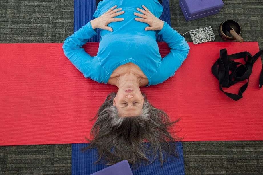 Marianne Bergonzi leads a yoga practice for Harvard employees at Monks Library in Harvard University Health Services. Bergonzi first took up yoga practice when she was 50 years old.