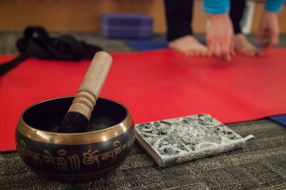 A Tibetan singing bowl and book of quotes create a serene environment.