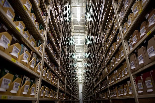 The Harvard Depository is a massive storage facility that houses more than half of the University's 17 million-volume collection (photo 1). Patrick O'Brien (photo 2), systems and special projects manager, is a member of the team that oversees the operation, which includes numerous phases of preparation (photo 3).