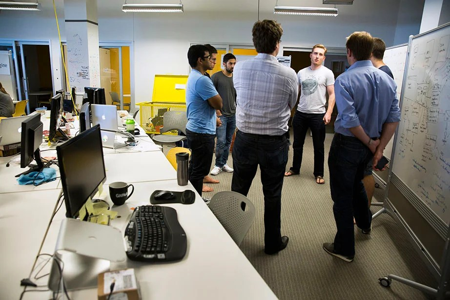 Joe Adelmann, a 2013 Harvard Kennedy School graduate (center), leads a morning meeting with the team from Censio, a usage-based insurance platform that enables auto insurers to reward customers who drive safely.