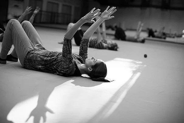 Dance Director and Senior Lecturer Jill Johnson teaches students in the classroom for the Harvard Dance Project. The students rehearse in the Harvard Dance Center at Harvard University. Whitney Cover, Ed.M. '15, (left) warms up during class. Stephanie Mitchell/Harvard Staff Photographer