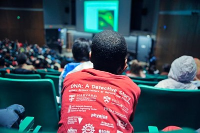 "A sea of DNA T-shirts (photo 1) filled Science Center B as hundreds gathered for Harvard's School of Engineering and Applied Sciences' annual holiday lecture. This year, Professor Howard Stone of Princeton University helped the youngsters crack the universal code and structure of DNA (photo 2), accompanied by his lecture, ""DNA: A Detective Story."" With parents participating, Lindsey Smilack and her son, Edwin, of Cambridge fashioned DNA molecules from pipe cleaners (photo 3)."