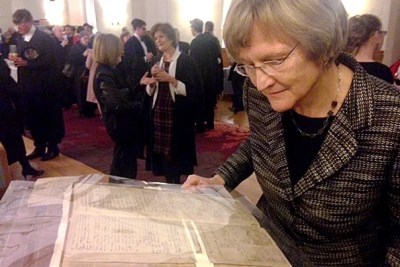 While at the University of Cambridge, Harvard President Drew Faust (photo 1) examined a 17th-century registration book  bearing the only known signature of a 1624 Emmanuel College matriculant named John Harvard (photo 2). Faust delivered the Sir Robert Rede Lecture at the University of Cambridge's historic Senate House.