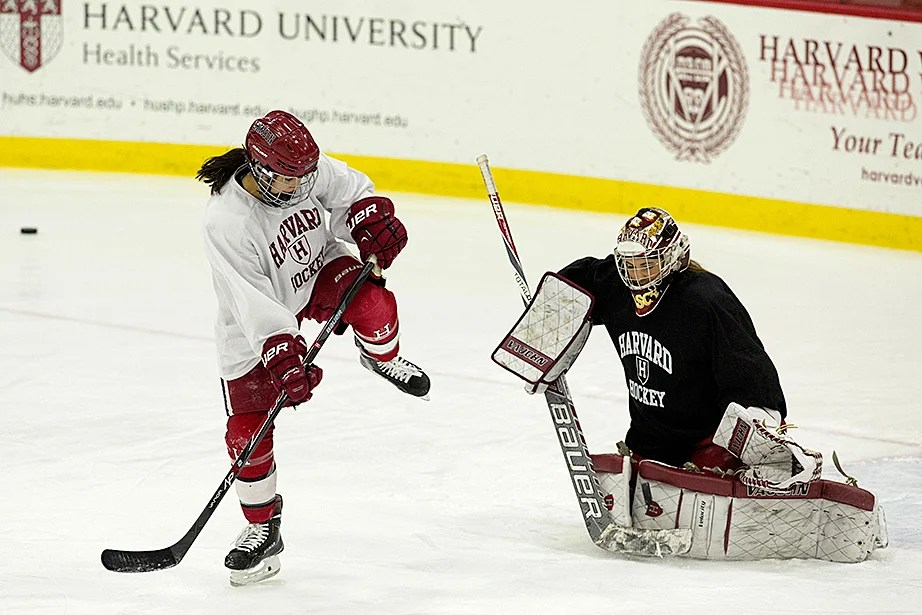 Miye D'Oench '16 high-steps as she flicks a puck toward goalie Emerance Maschmeyer '16 during practice. Jon Chase/Harvard Staff Photographer