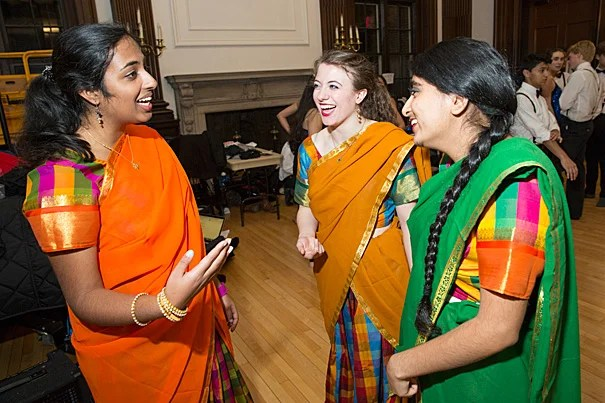 """As the largest student-run production, Ghungroo allows the students to tap their talents. Priyanka Kumar '18, (from left, photo 1), Lia Raynor '17, and Herman Kaur Bhupal '16 share a laugh after assisting each other with their outfits. Even the traditional — men in white shirts and suspenders — finds a place in the production (photo 2). Dancers practice before the show at First Church in Cambridge (photo 3). """"We're not technique-oriented,"""" explained Radhika Rastogi '15, the dance director. """"We're not out to impress the audience. It's always more about energy and enthusiasm."""""""