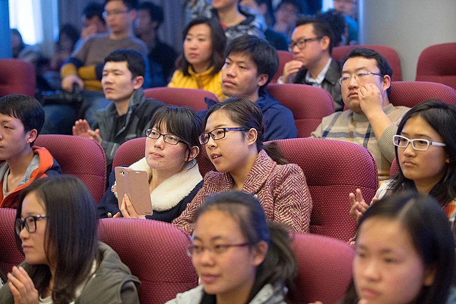 Tsinghua University students share a moment while using smart phones to record Drew Faust's lecture.