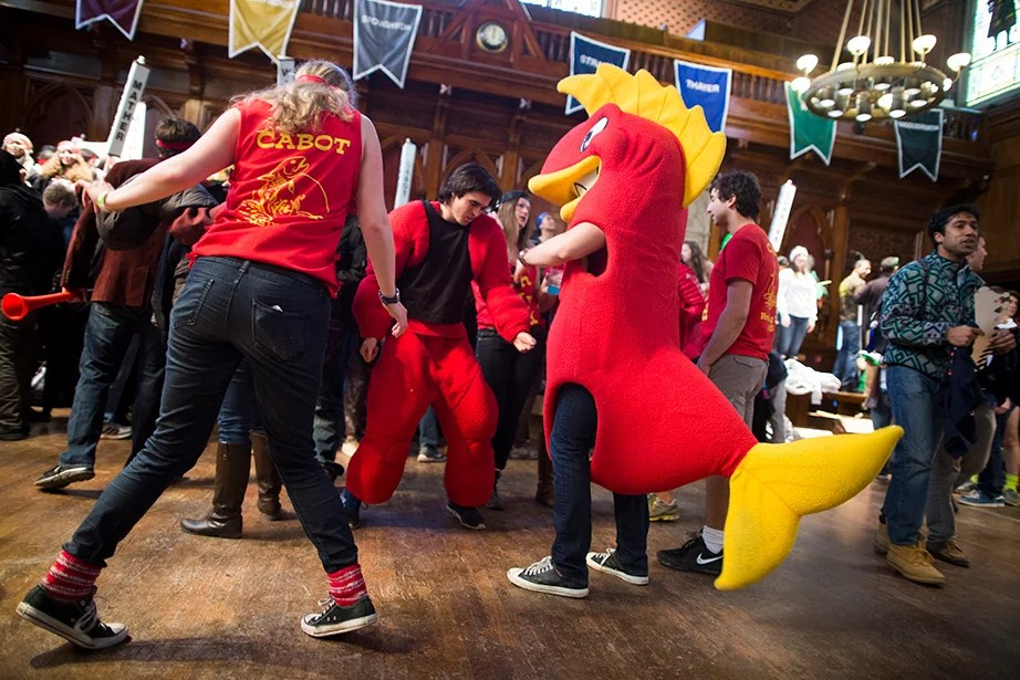 In Annenberg Hall, Lelaina Vogel '15 (left) from Cabot House dances with Chris Willis '17, who was dressed as the Cabot House mascot, a fish. Stephanie Mitchell/Harvard Staff Photographer