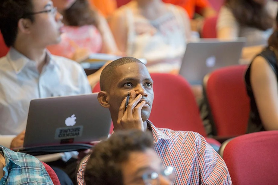 A student ponders Edward Glaeser's lecture inside Jefferson Hall. Kris Snibbe/Harvard Staff Photographer