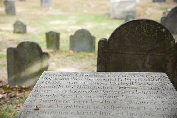 Executive Director of the Cambridge Historical Commission Charles Sullivan tours through the Old Burial Ground in Harvard Square where numerous notable Harvard figures are buried. Pictured here is a tombstone with the name Wadsworth. Stephanie Mitchell/Harvard Staff Photographer
