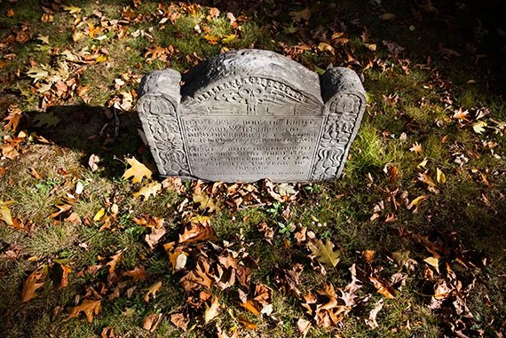 Executive Director of the Cambridge Historical Commission Charles Sullivan tours through the Old Burial Ground in Harvard Square where numerous notable Harvard figures are buried. Pictured here is a skull that decorates a tombstone. Stephanie Mitchell/Harvard Staff Photographer