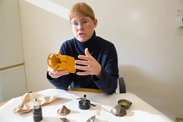"Bonnie Docherty, a senior instructor at Harvard's International Human Rights Clinic, traveled to Geneva to advocate for stronger regulations on incendiary devices, which she calls ""exceptionally cruel weapons."" Here she shows inert pieces of cluster munitions, another inhumane weapon, which she helped ban."