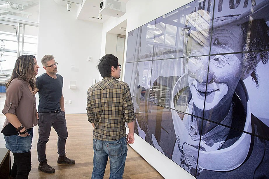 """Sarah Newman (from left) and Matthew Battles work with technology fellow Ming Tu on """"Your Story Has Touched My Heart."""" The photo of the clown is a sample image used to test the screen. """"The team's projects infuse traditional modes of academic inquiry with an enterprising spirit of hacking, making, and creative research,"""" says Battles."""