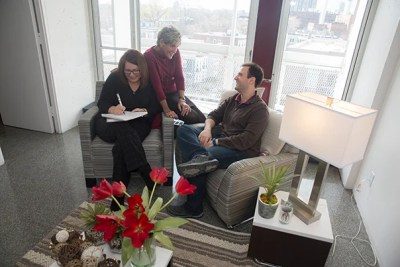 Kathryn Deveau (from left), Harvard University Housing Property Manager, talks with area manager Pamela Cornell (center) and Matheus Fernandes, doctoral student in the Harvard John A. Paulson School of Engineering and Applied Sciences. They are sitting on furniture free of chemical flame retardants, which is being added to Peabody Terrace's furnished apartments as part of a renovation project.