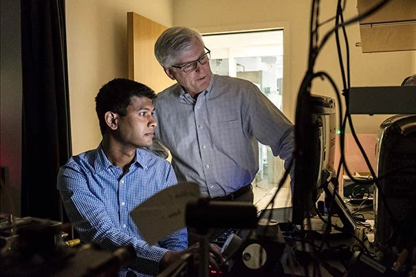 Rahul Palchaudhuri (left), postdoctoral fellow, and David Scadden, co-director of the Harvard Stem Cell Institute, look at real-time images of blood stem cells settling into bone marrow.