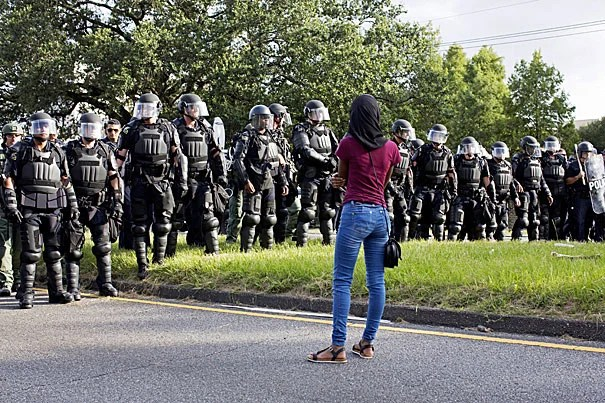 A woman watches as police in riot gear clear the street of demonstrators in front of the Baton Rouge Police Department on July 9. Longstanding tensions between police and African-Americans was discussed by Harvard Professor Ronald S. Sullivan.