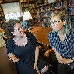 "Inside the Dudley House library, Vanessa Zoltan, M.Div. '15 (left), proctor and member of the Board of Freshman Advisers, and Ariana Nedelman, M.Div. candidate '18, HDS staff member, discuss their new podcast ""Harry Potter and the Sacred Text,"" which looks at the famous books as instructive and inspirational texts."