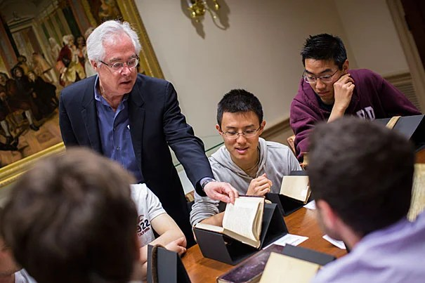 """Louis Menand (left) will be awarded the National Humanities Medal by President Obama. He is pictured with Bowen Lu '17 examining a volume of """"The Brothers Karamazov"""" by Dostoyevsky from 1881."""