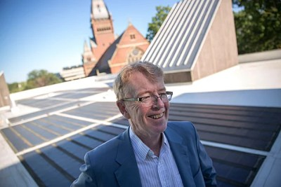 """Atop the roof of the Science Center with solar panels in the background, SEAS/EPS Professor Michael McElroy talks about his new book, """"Energy and Climate: Vision for the Future,"""" on the global energy challenge with climate change."""