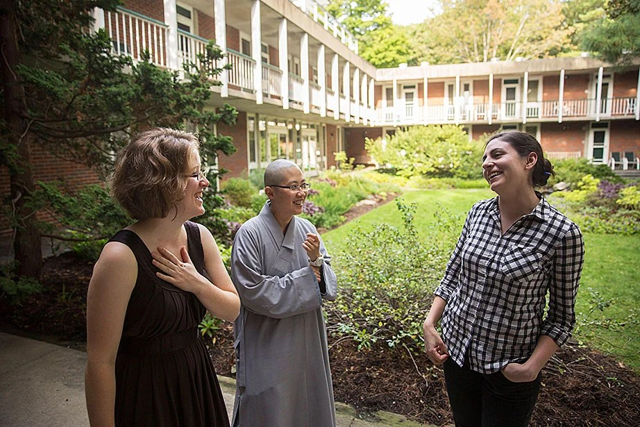 """Center for the Study of World Religions residents (from left) Melissa Coles, a student at Harvard Divinity School; the Ven. Changshen Shi Wang, visiting assistant professor at HDS; and Sara Klingenstein, a student at the Graduate School of Arts and Sciences, chat in the center's courtyard. """"Residents are a microcosm of the larger community at HDS: a non-sectarian school of religious and theological studies that is home to a diverse community of scholars and practitioners,"""" Coles said."""