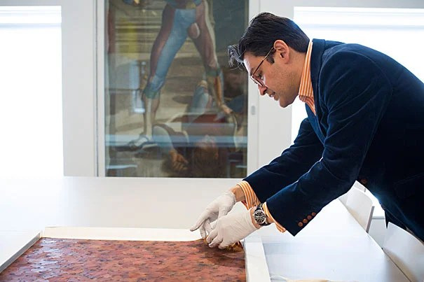 """Director of Harvard's Straus Center for Conservation and Technical Studies Narayan Khandekar examines an unused swatch from """"A Flor de Piel,"""" a giant tapestry of rose petals that will soon be on view as part of the Harvard Art Museums' upcoming special exhibit """"Doris Salcedo: The Materiality of Mourning."""""""