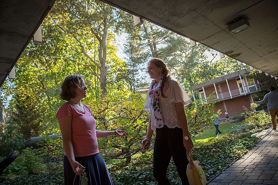 Melissa Coles (from left) and teaching fellow Laura Thompson have a heart-to-heart in the courtyard.
