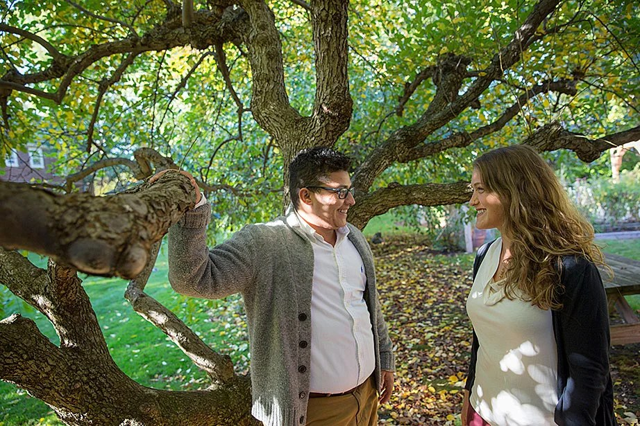 """Nina Bryce (right) and her fiancé, Soltan Bryce, talk beneath a canopy of foliage in the Center for the Study of World Religions garden. """"As an interfaith couple, making the CSWR our home this year has been a beautiful experience. The resident community celebrates learning from one another while exploring complex questions related to religion,"""" said Bryce."""