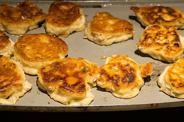 Corn cakes made with green onion and dried cranberries sizzle on the griddle. Wampanoag chef Sherry Pocknett cooked traditional foods to share with students at Pforzheimer House as part of the Native American House Fellows Program. The tasting took place at Faculty Dean Anne Harrington's residence. Jon Chase/Harvard Staff Photographer
