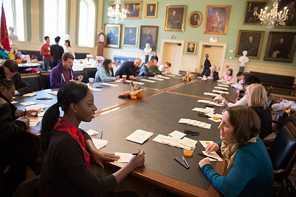 "Harvard Center for African Studies associate director Maggie Lopes (right) and center communications officer Mbessin Sonko (left) write notes of thanks during the Annual FAS Giving Thanks event at University Hall. ""I started [at the Center for African Studies] about a month and a half ago and my team has really been that core of strength since I've gotten here,"" said Sonko."